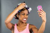 stock photo of african american hair styles  - An African American woman putting on makeup - JPG