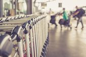picture of trolley  - Close up trolleys luggage with blurred of passenger in airport retro filter effect - JPG