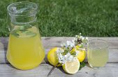 stock photo of mints  - Lemonade with mint and lemons on wood and grass background - JPG