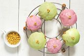 foto of icing  - Cupcakes with pink and green icing on the grid sugar beads in a cup on a white wooden background - JPG