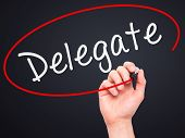 stock photo of mandates  - Man Hand writing Delegate black marker on visual screen - JPG