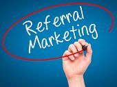 stock photo of joining hands  - Man Hand writing Referral Marketing with marker on transparent wipe board - JPG