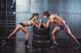 pic of conflict couple  - Athlete muscular sportsmen man and woman with hands clasped arm wrestling challenge between a young couple Crossfit fitness sport training lifestyle bodybuilding concept - JPG