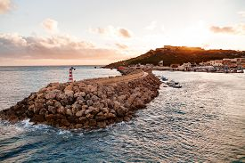 pic of gozo  - Entrance in bay seafront with lighthouse on seafront at sunset - JPG