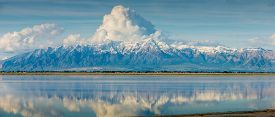 stock photo of reflections  - Wasatch Mountain Range Utah Snow capped clouds reflecting in Salt Lake blue sky panoramic pano - JPG