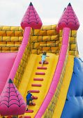 foto of inflatable slide  - Young children climb steps in inflatable bumper castle - JPG