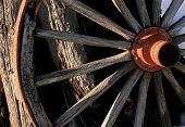 stock photo of wagon wheel  - light and shadow on an old west wagon wheel - JPG