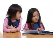 image of storytime  - two sisters share a book together - JPG