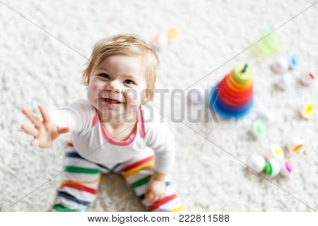 poster of Adorable cute beautiful little baby girl playing with educational toys at home or nursery. Happy healthy child having fun with colorful wooden rainboy toy pyramid. Kid learning different skills