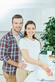 Affectionate husband and wife looking at camera with smiles in the kitchen poster