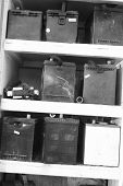 image of shelving unit  - A selection of used car batteries sitting on a shelving unit in a junk yard. Black & White. ** Note: Slight blurriness, best at smaller sizes - JPG