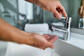 Man washing hands in bathroom sink at home checking temperature touching running water with hand. Cl poster