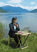 relaxed businesslady works by the lakeside