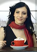 a girl is drinking coffee in a cafeteria