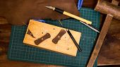 Leather craft. leather parts being created on a cutting board. Leather craft tools around the piece. poster