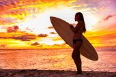 Surfer bikini girl on Hawaii beach holding surf board watching ocean waves at sunset. Silhouette of  poster