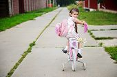 foto of bagpack  - Young school girl with bagpack rides her pink bike to school - JPG