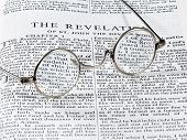 pic of revelation  - Old fashioned round reading glasses laying on a page from the bible on the revelation - JPG