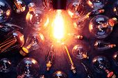 Vintage old light bulb glowing yellow on rough dark background surrounded by burnt out bulbs. Idea,  poster