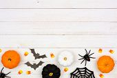 Halloween Bottom Border With Black, Orange And White Decor And Candy Over A White Wood Background. T poster