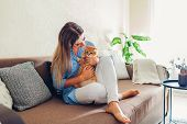 Playing With Cat At Home. Young Woman Sitting On Couch And Hugging Pet. poster