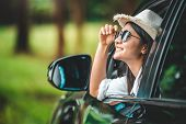 Happy Woman Hand Holding Hat Outside Open Window Car With Green Forest Woods Mountain Background. Pe poster