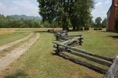 picture of split rail fence  - A colonial era split rail fence along a dirt road  - JPG