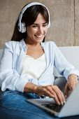 Photo of a cheery positive happy young woman indoors at home using laptop computer listening music w poster
