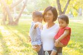 Beautiful Young Asian Mother Carrying Little Boy And Girl In The Park, Asia Woman Happy Having Son A poster