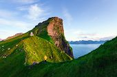 Kallur lighthouse on green hills of Kalsoy island, Faroe islands, Denmark. Landscape photography poster