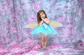 foto of full cheeks  - Ballerina wearing an aqua tutu and fairy wings stands in a room filled with pink and grey - JPG