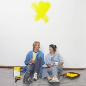 Couple having coffee on tarp with paint and paintbrushes