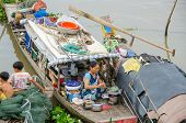 CHAU DOC, VIETNAM - JANUARY 2: Unidentified fisherman's wife cooks a meal on her wooden boat while h