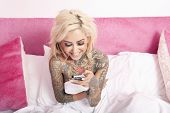 picture of partially nude  - Naked woman with tattoo sitting in bed reading text message in mobile phone - JPG