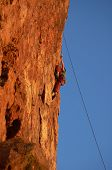 Rock Climber On Vertical Cliffside