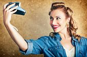 foto of selfie  - Old Fashion Female Photographer With Fifties Style Hair Rolls Taking Self Portrait With A Vintage Camera In A Depiction Of A Selfie - JPG