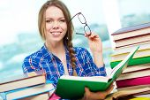 stock photo of diligent  - Portrait of diligent student looking at camera with open book in hands - JPG