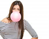 Portrait Of A Young Woman Blowing Bubblegum against a white background