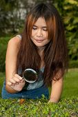Pretty Asian Woman Looking Butterfly With Magnifying Glass.