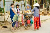 CHAU DOC, VIETNAM - JANUARY 3: Unidentified seller of raw chickens sells her products to local women