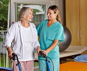 Physiotherapeuten helfen senior Woman mit Walker an Heilgymnastik