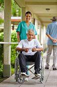 Happy nurse driving a senior man in wheelchair in a clinic