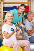 Happy senior man and woman in gym doing fitness in a nursing home