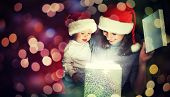 stock photo of birthday hat  - Christmas magic gift box and a woman happy family mother and Child baby - JPG