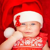 Closeup portrait of sweet little baby wearing Santa hat with stylish bow, red background, celebrating Christmas at home, joy and fun concept