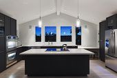 pic of oven  - A modern kitchen in a luxury house with lights on and blue sky - JPG