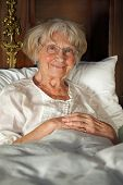 pic of nightgown  - Happy grey haired senior lady wearing glasses relaxing in bed in her nightgown giving the camera a beautiful smile - JPG