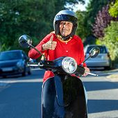 Smiling Old Lady On A Scooter
