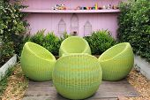 picture of lawn chair  - Rattan furniture on lawn in a green garden - JPG