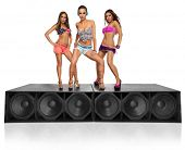 three seductive young girls standing on speakers